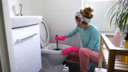 banheiro : Woman with a rubber glove cleans a toilet bowl using means for cleaning