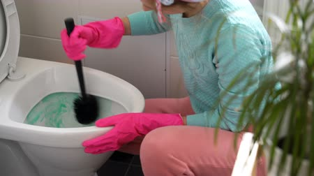 домохозяйка : Woman with a rubber glove cleans a toilet bowl using means for cleaning