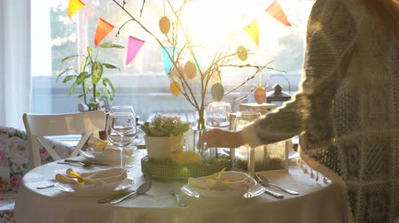 villa : Young woman and her little daughter are setting easter festive table with bunny and eggs decoration
