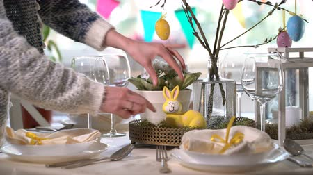столовые приборы : Young woman is setting easter festive table with bunny and eggs decoration Стоковые видеозаписи