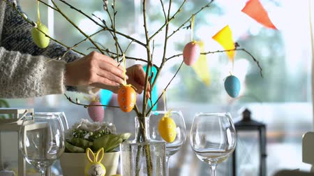 оформление : Young woman is setting easter festive table with bunny and eggs decoration Стоковые видеозаписи