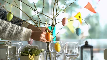 zastawa stołowa : Young woman is setting easter festive table with bunny and eggs decoration. Slow Motion
