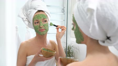しかめっ面 : a young woman with a white towel put on her face a green moisturizing mask in a bathroom