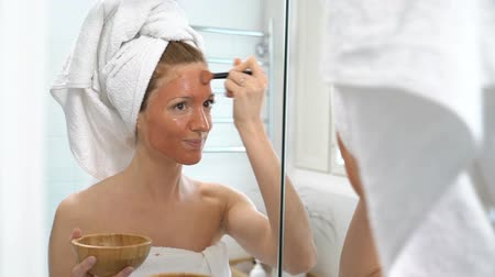 obličejový : a young woman with a white towel put on her face a brown moisturizing mask in the bathroom