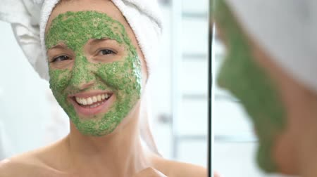 arcszín : a young woman with a white towel put on her face a green moisturizing mask smiling at the camera and making funny face