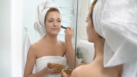 pepinos : Young woman with a white towel put on her face a moisturizing mask in the bathroom Vídeos
