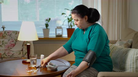 female measurements : Old age people health problem concept. An elderly woman measures blood pressure at home. Stock Footage