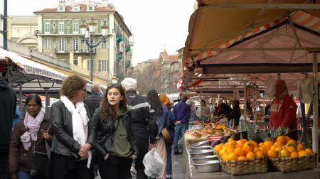 venda : NICE, FRANCE - MARCH 29, 2018: The famous open-air market in the old town of Nice in the early morning. Counters with vegetables and fruits