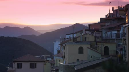 virgin forest : The setting sun illuminates the roofs of a medieval town in the mountains. Perinaldo, Italy.