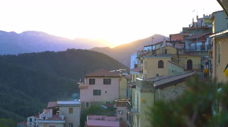 virgin forest : Early foggy morning in an alpine town. The rising sun illuminates the roofs of a medieval town in the mountains.. Perinaldo, Liguria, Italy.