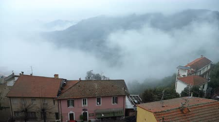 virgin forest : Early foggy morning in the Alpine town. Fog from the mountains makes its way along the medieval streets. Perinaldo, Liguria, Italy.