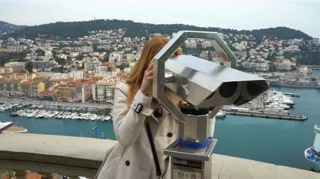 looking distance : Traveler woman watching through the stationary binoculars at a scenic overlook in Nice, France Stock Footage