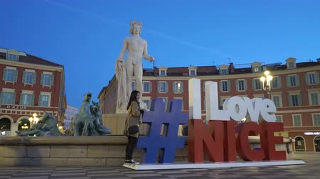 hashtag : NICE, FRANCE - MARCH 28, 2018: Fountain du Soleil with a marble statue of Apollo adorned with the installation of hashtag I love Nice at night