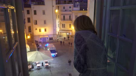 scény : A night incident in the city. Ambulance car on the street. Excited Young woman looks out the window of her house. First aid, life insurance, terrorist threat Dostupné videozáznamy