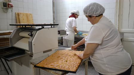 muffin : Traditional Italian family bakery. A female baker cuts a big pie into pieces. Real people.