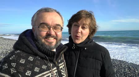 coppia senior : A Mature couple walks on the Mediterranean beach on a Sunny winter day. Slow motion