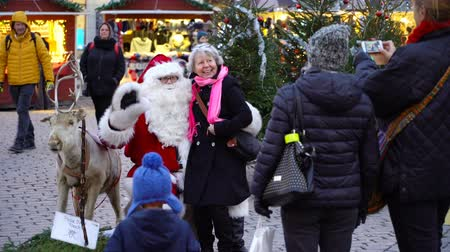 elfo : HELSINKI, FINLAND - DEC 17, 2017: An elderly woman is happy to sit on Santas lap. Children and parents meeting Santa Claus in the center of Helsinki on the eve of Christmas. Stock Footage