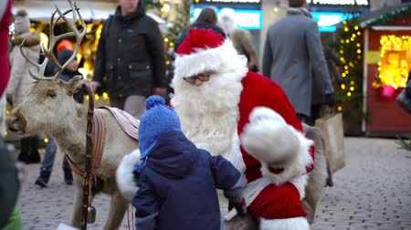elfo : HELSINKI, FINLAND - DEC 17, 2017: A little boy is happy to sit on Santas lap. Children and parents meeting Santa Claus in the center of Helsinki on the eve of Christmas.
