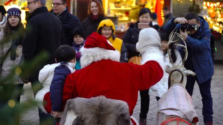 elfo : HELSINKI, FINLAND - DEC 17, 2017: Santa gives gifts to children at the Christmas fair. Children and parents meeting Santa Claus in the center of Helsinki on the eve of Christmas.
