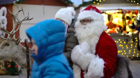 elfo : HELSINKI, FINLAND - DEC 17, 2017: A little girl is happy to sit on Santas lap. Children and parents meeting Santa Claus in the center of Helsinki on the eve of Christmas.
