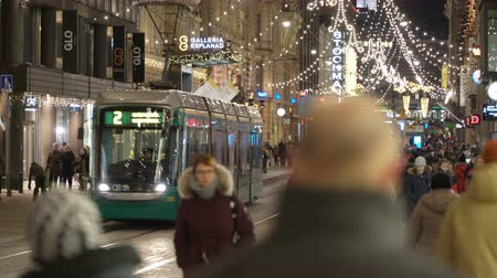 tramwaj : HELSINKI, FINLAND - DEC 17, 2017: A lot of people and bright decorations on the central street of city during Christmas celebrations and total sales.