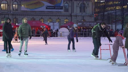 bezmotorové létání : HELSINKI, FINLAND - FEBRUARY 15, 2018: Ice skating rink in Helsinki city centre. Tourist and locals, сhildren and adults enjoying skating and Finnish winter activities