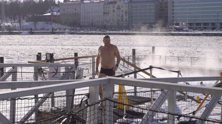 boldness : HELSINKI, FINLAND - FEBRUARY 24, 2018: People swim in open air sea pool in the center of Helsinki in winter. Allas Sea Pool is a sauna and a saltwater pool open all year round.