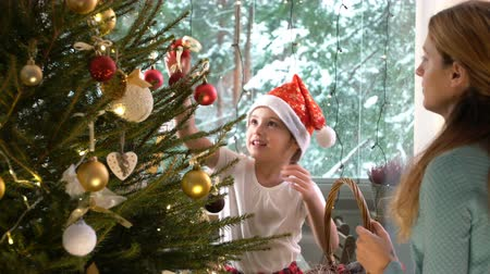 elves : Little cute girl in a red hat with her mom decorate the Christmas tree