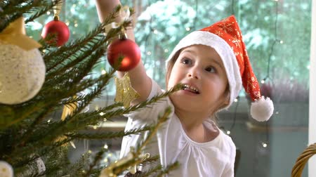 elfo : Little cute girl in a red hat with her mom decorate the Christmas tree