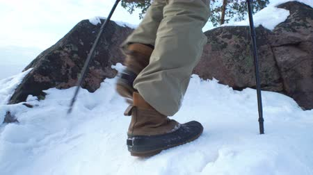sırt çantasıyla : Group of young people hiking in mountains in winter. Backpackers walking on snow in Scandinavia. Close-up of a tourists foot in trekking boots with sticks for Nordic walking. Stok Video