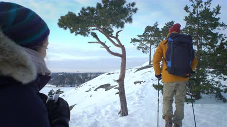 kemping : Group of young people hiking in mountains in winter. Backpackers walking on snow in Scandinavia, help each other, take pictures and enjoy nature