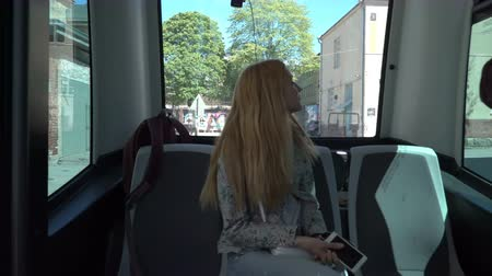 автобус : HELSINKI, FINLAND - MAY 25, 2018: Young woman in automated remotely operated bus in Helsinki. Unmanned public transport on street.