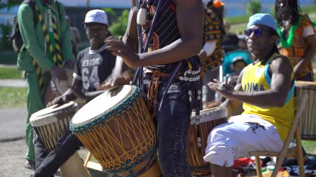 percussão : HELSINKI, FINLAND - MAY 26, 2018: Young natives of Africa and the locals dance and play traditional folks drums in a City Park in Helsinki. Vídeos
