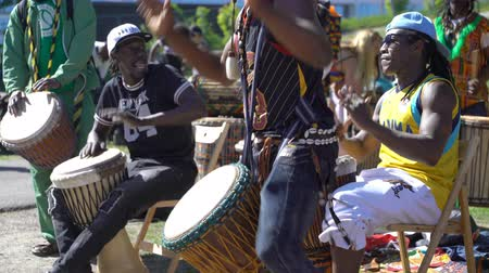 pessoal : HELSINKI, FINLAND - MAY 26, 2018: Young natives of Africa and the locals dance and play traditional folks drums in a City Park in Helsinki. Vídeos