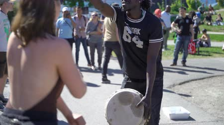 ırklararası : HELSINKI, FINLAND - MAY 26, 2018: Young natives of Africa and the locals dance and play traditional folks drums in a City Park in Helsinki. Stok Video