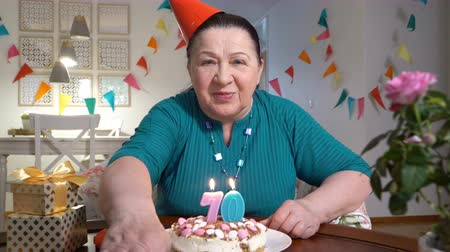 uzun ömürlü : Happy senior woman holding cake to web camera while celebrating birthday with her family via video chat Stok Video