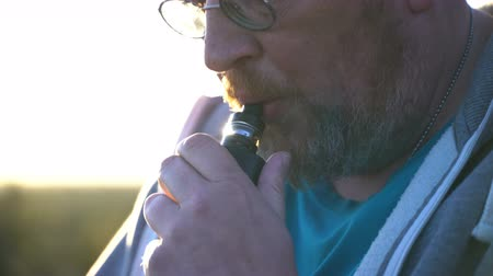 smettere di fumare : Mature bearded man sitting on the rocks in the park and smoking electronic cigarette