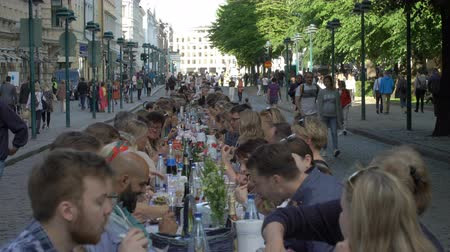 all ages : ESPOO, FINLAND - JUNE 12, 2018: A lot of people eating and drinking at the same table. Traditional common table for everyone in honor of the Day of the City in the center of Helsinki. Stock Footage