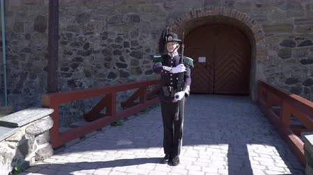 Норвегия : OSLO, NORWAY - JULY 04, 2018: Armed guardsman in a beautiful uniform in the ancient castle and fortress of Akershus Стоковые видеозаписи