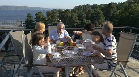 norveç : A big happy family has dinner on the open terrace on the roof of the house. Tea party on the summer terrace on the sea coast Stok Video