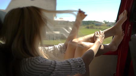 barefooted : A young redhead woman enjoys traveling by car throws her legs on the window. Slow motion. Stock Footage