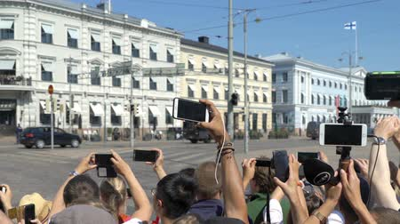 putin : HELSINKI, FINLAND - JULY 16, 2018: A lot of people filming the motorcade Donald Trump on the streets of the city using smartphones. Meeting trump and Putin in Helsinki. Stock Footage