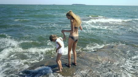 солнечные ванны : A young slender woman and her sweet daughter are walking and playing with the sea waves among the coastal rocks on the beach in Finland. Стоковые видеозаписи