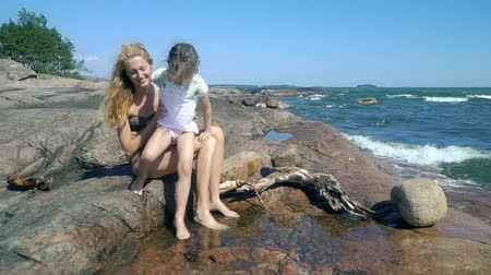 baltské moře : A young slender woman and her sweet daughter are playing in rock pools among the coastal rocks on the beach in Finland. Dostupné videozáznamy