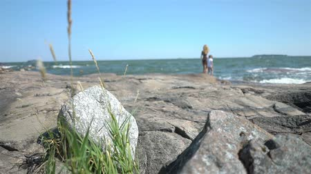 finlandiya : A young slender woman and her daughter are walking among the coastal rocks on the beach in Finland. Stok Video