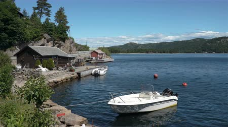 motorbot : LINDESNES, NORWAY - JULY 07, 2018: Traditional rustic Scandinavian summer landscape. Cottages boathouse and boats on the shores on the south coast of Norway