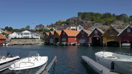Скандинавия : HOLLEN, NORWAY - JULY 09, 2018: Traditional rural red wooden Norwegian garages for boats on the coast of North Sea, Norway.