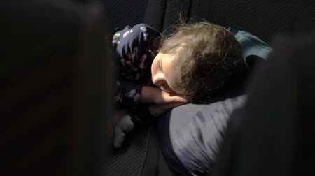 ülés : The little girl sleeping in the back seat of the car. Stock mozgókép