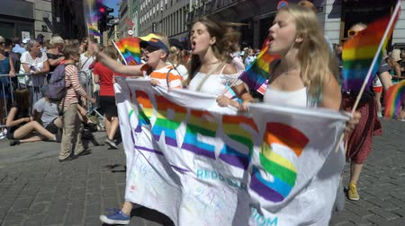 солидарность : OSLO, NORWAY - JUNE 30, 2018: A lot of fancy-dress people with rainbow flags dance, sing and laugh in the street. The Pride Parade, the highlight of Oslo Pride Week, is a huge, vibrant parade filling the city streets. Стоковые видеозаписи