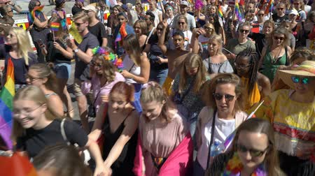 af : OSLO, NORWAY - JUNE 30, 2018: A lot of fancy-dress people with rainbow flags dance, sing and laugh in the street. The Pride Parade, the highlight of Oslo Pride Week, is a huge, vibrant parade filling the city streets. Stok Video